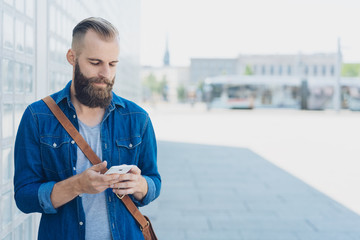 Bearded man reading a sms on his mobile phone