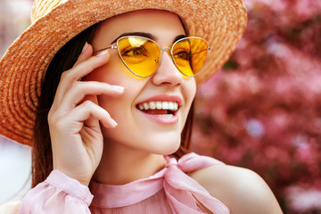 Outdoor close up portrait of young beautiful happy smiling woman wearing yellow sunglasses, straw hat, posing in street. Copy, empty space for text