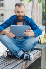 Handsome young man using a tablet outdoors