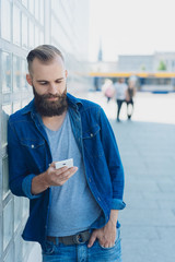 Casual bearded man using his mobile phone
