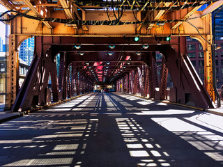 """Shadows from Chicago's elevated """"'el"""" track make interesting patterns on the street below during midday."""