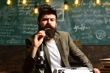 Man with beard on thinking face. Bearded man with retro typewriter and microscope. Scientist make research in university. Businessman with glasses sit at desk. Research or knowledge and innovation