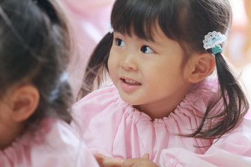 教室で遊び着を着る幼児(3歳児) (白バック)