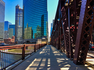 Chicago's elevated train tracks cast shadows on Lake Street and sidewalk along the river in downtown Loop.