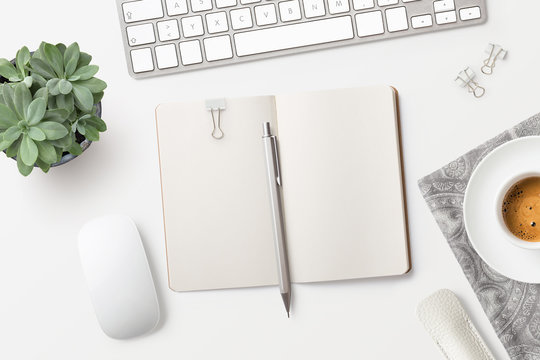 bright minimalist workspace / desktop with blank open notebook, office supplies, coffee and succulent plant on a white background - top view, copyspace
