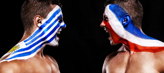 Soccer or football fan with bodyart on face with agression - flags of Uruguay vs France playoff. Sport Concept with copyspace.