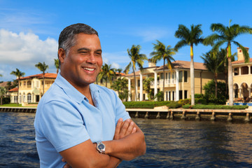 Handsome Hispanic man outdoors by waterfront homes