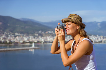 woman with hat in white t-shirt making photo, travel concept, photographer tourist with mountains sea and city on background.