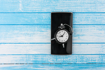 Black Big Screen Smart Phone With Reflection And Twin Bell Retro Alarm Clock On It On High Contrast Blue And White Wood Background