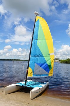 A small sailing catamaran resting on the beach on Sandpiper Bay,St.lucie River in Central Florida