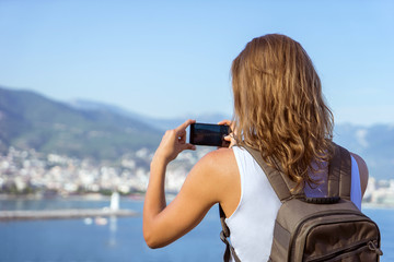 traveling woman making photo of cityview, travel concept, mounta