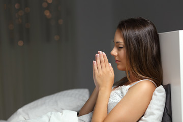 Woman praying in the night in a bed at home