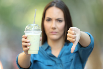 Angry woman holding a smoothie with thumbs down