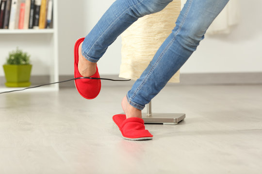 Woman stumbling with an electrical cord at home