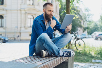 Young man sat on park bench using tablet