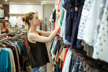 Woman looking clothes in the shopping mall, seasonal sale or thrifting concept