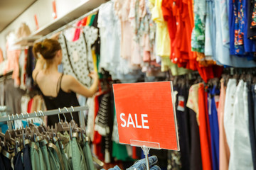 Woman looking clothes on discount in the shopping mall, seasonal sale concept