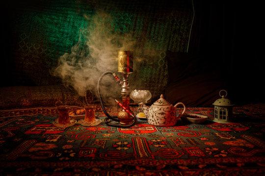 Hookah hot coals on shisha bowl making clouds of steam at Arabian interior. Oriental ornament on the carpet eastern tea ceremony. Stylish oriental shisha in dark with backlight.