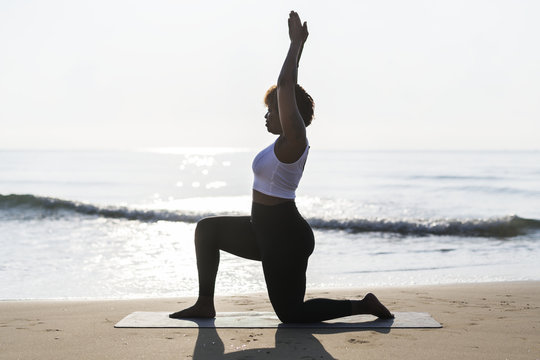 African American woman practicing yoga at the beach
