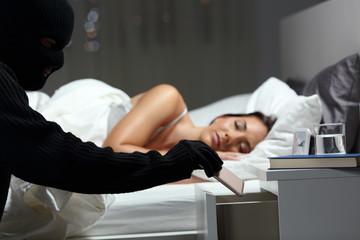 Thief stealing a phone in a bedroom - fototapety na wymiar