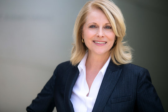 Smiling head shot of a mature older female business leader, warm, friendly, likable, executive professional