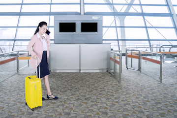 Young businesswoman conversed by phone in airport