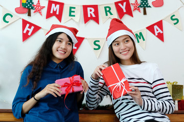 Young cute asian women smiling and holding Christmas gift boxes at Christmas celebration party