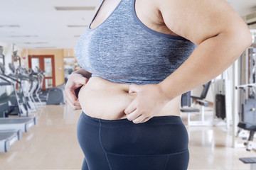 Young woman holding excessive belly fat
