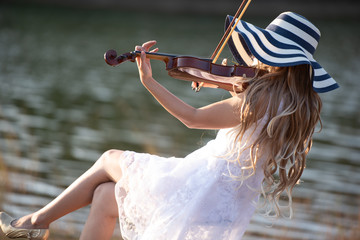 Young girl with hat playing the violin at lake.