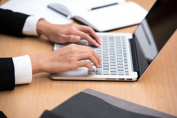 Close up of female hands typing on laptop computer keyboard.