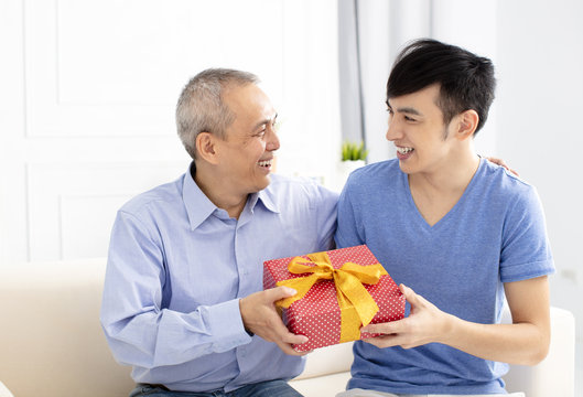 happy family celebrating and son giving gift to father