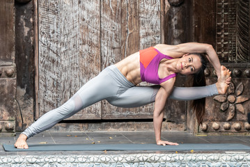 Young healthy woman doing yoga exercises at home.