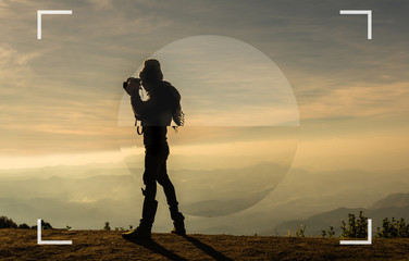 camera viewfinder with focusing the screen of silhouette of a photographer who shoots the mountains landscape when sunset time, Photographer concept