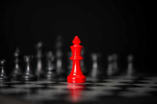 Red chess between black chess board game for competition and strategy, business success concept