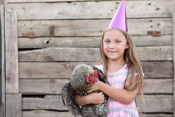 Young girl in pointed magic hat holds motley chicken in her hands and poses in front of camera in village courtyard. The concept of healthy lifestyle in nature, love of the world, respect for nature