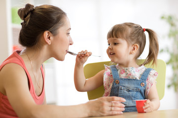 playful child girl spoon feeding her mother