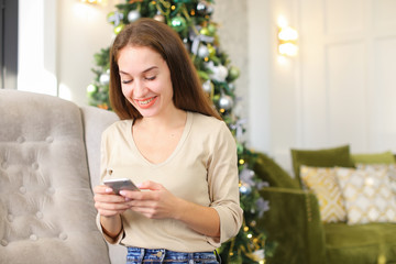 architect using tablet, smiling female laying on carpet near decorated pinetree watching photos in social networks. Pretty smiling girl with ponytail wearing white turtleneck jeans spending free time