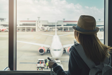 Young woman traveler with luggage holding passport looking at the airplan