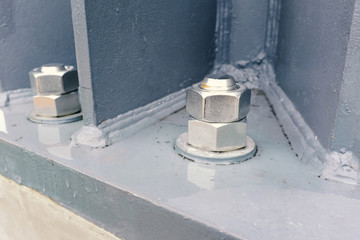 giant nut and bolt on base plate of metal pole