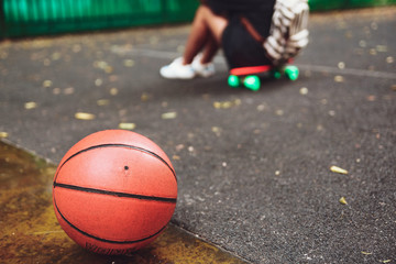 Closeup photo basketball ball with girl sitting on plastic orange penny shortboard on asphalt