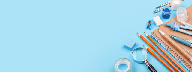 School stationary on blue background. Notebook, pens, pencils and other tools. Banner for website.