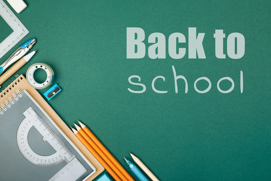 Student's stationary on green background and inscription Back To School. Preparation to school.