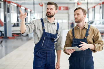Waist up portrait of two modern bearded mechanics walking across workshop and pointing away  while working in car service and repair center