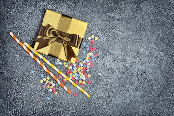 Golden shiny classic gift box with satin bow and cocktail straws with sprinkles or confetti as attributes of party