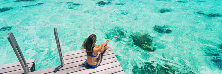 Wall Mural - Luxury beach vacation travel destination woman relaxing on idyllic paradise blue turquoise clear water for snorkeling. Banner panorama with background texture on ocean.
