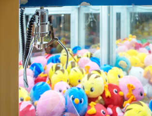 A mechanical arm selecting a random colorful dolls in a Claw capture device vending machine.