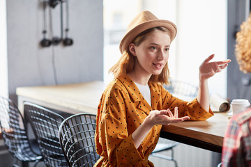 Young stylish businesswoman in hat discussing working points with her colleague in cafe