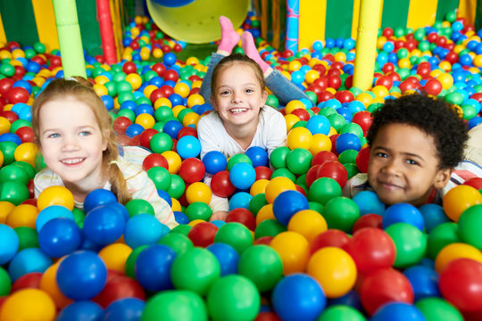 Colorful portrait of three happy kids smiling happily at camera while having fun in ball pit of children play center, copy space