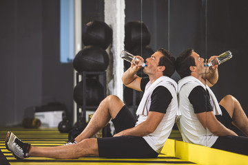 Full length side view pleased man drinking delicious beverage after hard workout in gym. He sitting on floor there