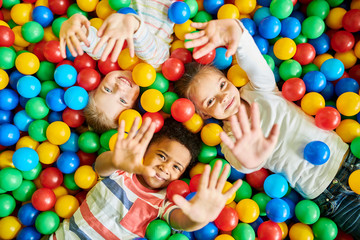 Fototapeta Above view portrait of three happy little kids in ball pit smiling at camera raising hands while having fun in children play center, copy space